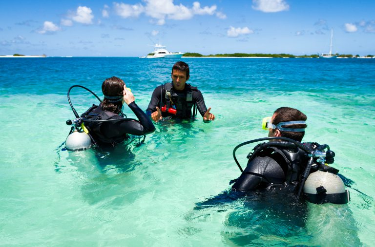 An instructor teaching new divers in shallow water