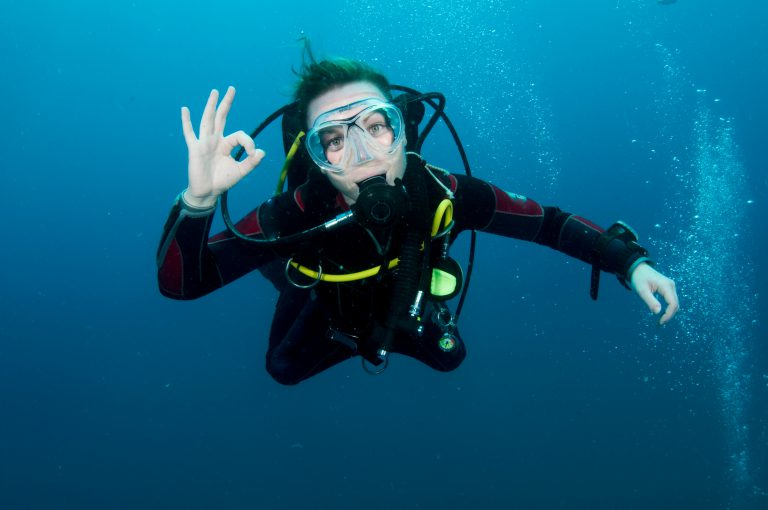 A beginning scuba diving student gives the OK signal.