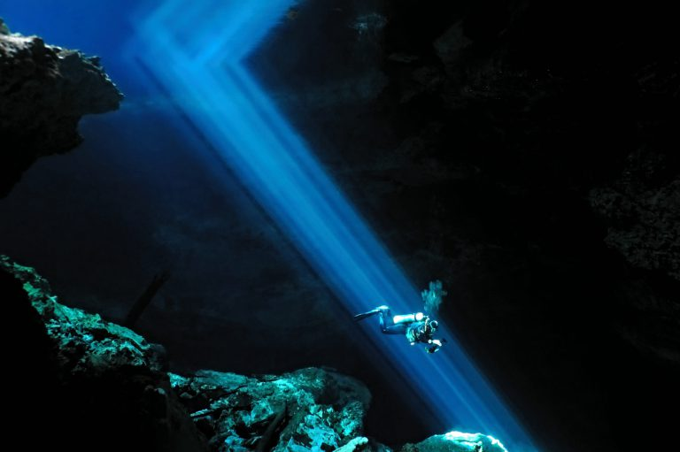 A diver descends along a beam of light in a Cenote.