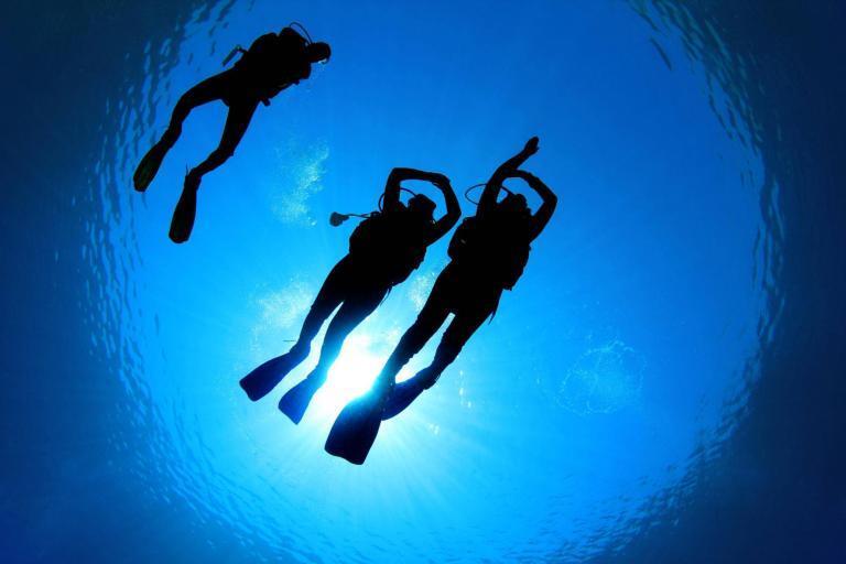 Three scuba divers practice underwater navigation.
