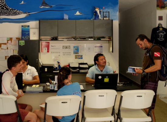 A view of the Blue Magic Scuba front desk with customers.